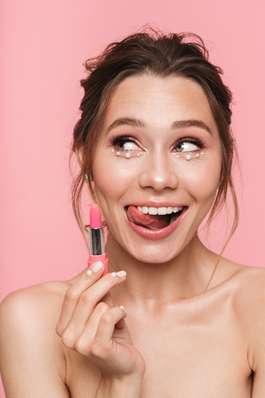 Photo pour Image of a pretty happy young woman posing isolated over pink wall background holding lipstick. - image libre de droit