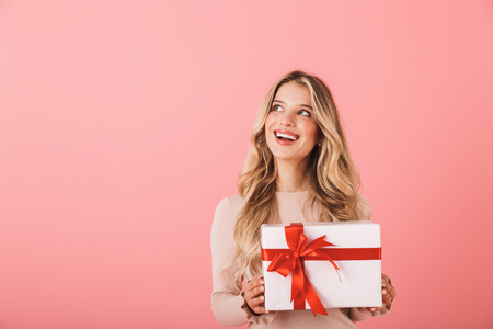 Foto de Portrait of a lovely blonde haired young woman standing isolated over pink background, holding gift box - Imagen libre de derechos