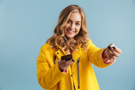 Image of pleased woman 20s wearing yellow raincoat holding mobile phone and listening to music via earphones isolated over blue background