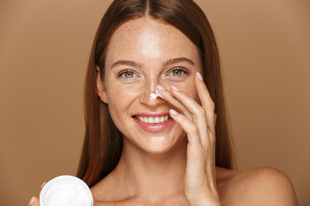 Foto de Beauty image of attractive shirtless woman smiling and holding jar with face cream isolated over beige background - Imagen libre de derechos