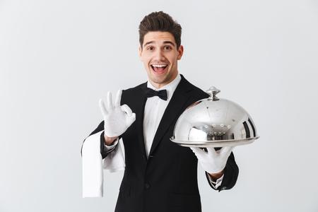 Foto de Happy young waiter in tuxedo holding serving tray with metal cloche and napkin, showing ok - Imagen libre de derechos