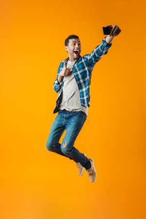 Photo pour Full length portrait of a happy young man wearing plaid shirt isolated over orange background, jumping, taking a selfie - image libre de droit