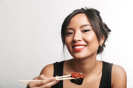 Photo pour Pretty happy asian woman sitting isolated over white background, eating sushi with chopsticks - image libre de droit