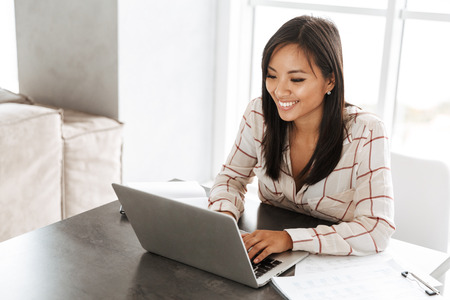 Photo for Image of asian beautiful woman 20s working on laptop while sitting at table indoor - Royalty Free Image