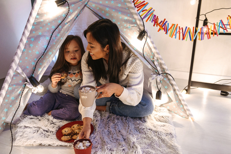 Photo pour Photo of happy asian family mother and daughter eating cookies while resting together at home in children playing tent - image libre de droit