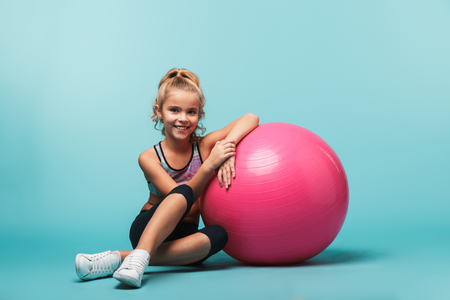 Photo pour Cheerful little girl wearing sport clothes leaning on a fitness ball isolated over blue background - image libre de droit