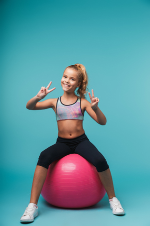 Foto de Cheerful little girl wearing sport clothes doing exercises with fitness ball isolated over blue background - Imagen libre de derechos