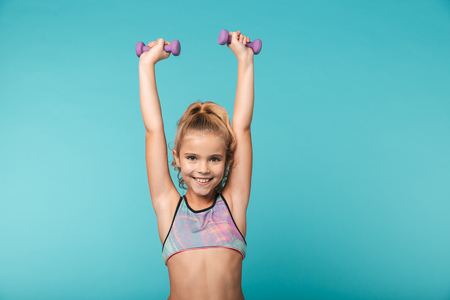 Photo for Smiling little sports girl doing exercises with dumbbells isolated over blue background - Royalty Free Image