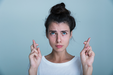 Photo pour Portrait of a casual beautiful young girl isolated over blue background, holding fingers crossed for good luck - image libre de droit