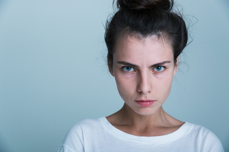 Photo pour Close up of an upset young casual girl isolated over blue background - image libre de droit