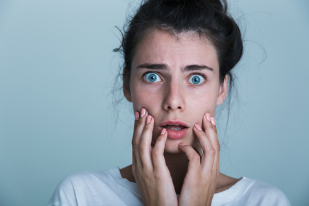 Photo for Close up of a shocked young woman wearing t-shirt isolated over blue background - Royalty Free Image