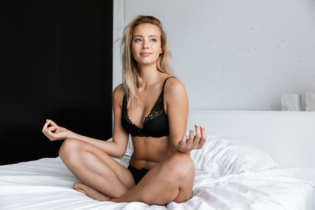 Photo pour Lovely young woman wearing lingerie sitting on bed with legs crossed - image libre de droit