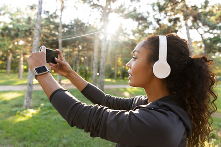 Portrait Of Pretty Woman 20s Wearing Black Tracksuit And Headphones Taking Selfie Photo On Cell Phone While Walking Through Green Park Royalty Free Images Photos And Pictures