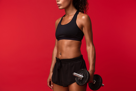 Foto de Image of athletic african american woman in black sportswear lifting dumbbell isolated over red background - Imagen libre de derechos