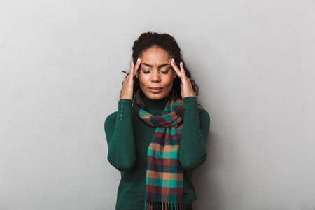 Photo for Desperate african woman wearing sweater standing over gray wall background, suffering from a strong migraine - Royalty Free Image