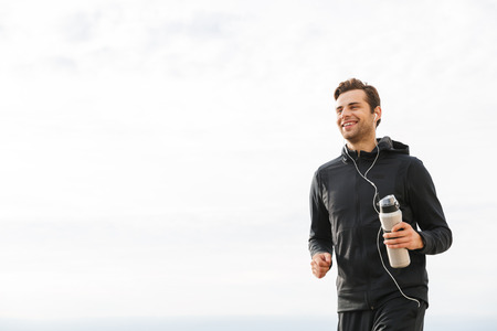 Photo pour Image of adult sportsman 30s in black sportswear and earphones working out and running by seaside - image libre de droit