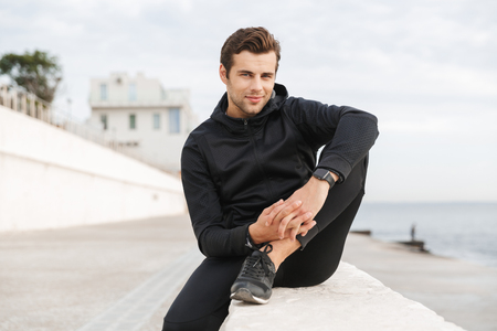 Foto de Image of sportive adult man 30s in black sportswear sitting on boardwalk at seaside - Imagen libre de derechos