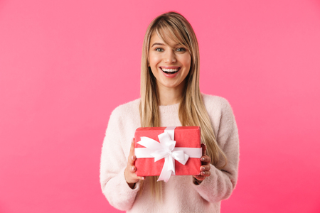 Foto de Cheerful young blonde girl standing isolated over pink background, showing gift box - Imagen libre de derechos