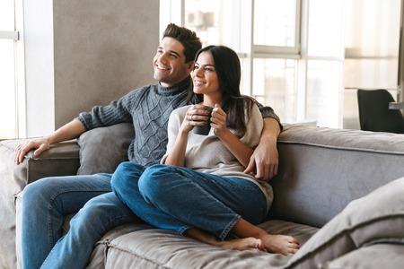 Foto de Happy young couple sitting on a couch at home, watching TV, drinking tea - Imagen libre de derechos