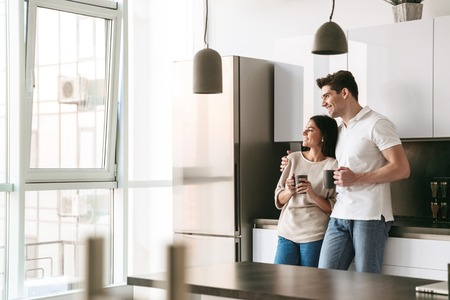 Photo pour Happy lovely young couple holding cups while standing at the kitchen at home, looking at the window - image libre de droit