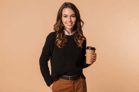 Photo pour Smiling young woman wearing sweater standing isolated over beige background, holding takeaway coffee cup - image libre de droit