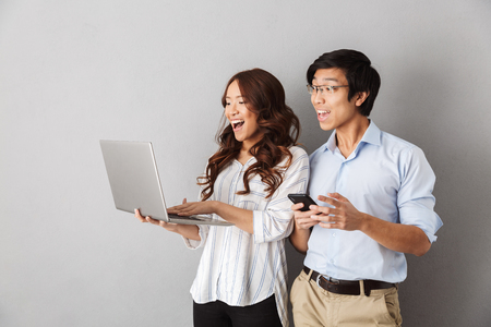 Photo pour Happy asian couple standing isolated over gray background, using laptop computer, holding mobile phone - image libre de droit