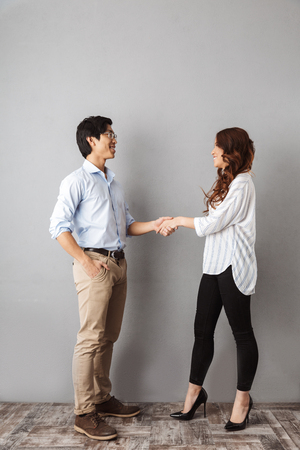Photo pour Full length of cheerful asian couple standing over gray background, shaking hands - image libre de droit