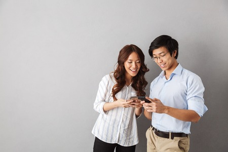 Photo pour Happy asian couple standing isolated over gray background, using mobile phones - image libre de droit