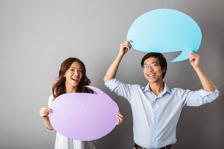 Photo pour Cheerful asian couple standing isolated over gray background, holding empty speech bubble - image libre de droit