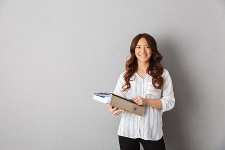 Photo pour Smiling asian business woman standing over gray background - image libre de droit
