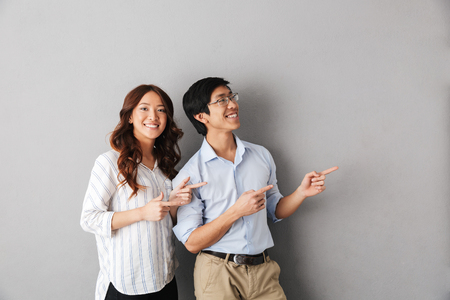 Foto de Cheerful asian business couple standing isolated over gray background, pointing fingers away at copy space - Imagen libre de derechos