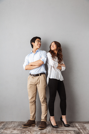 Foto de Full length of cheerful asian couple standing back to back over gray background - Imagen libre de derechos