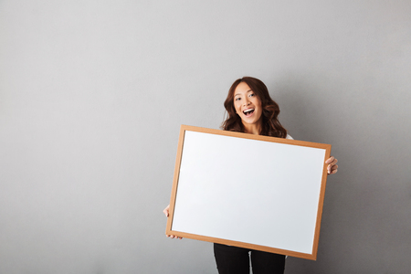 Photo pour Cheerful asian woman standing isolated over gray background, showing blank board - image libre de droit