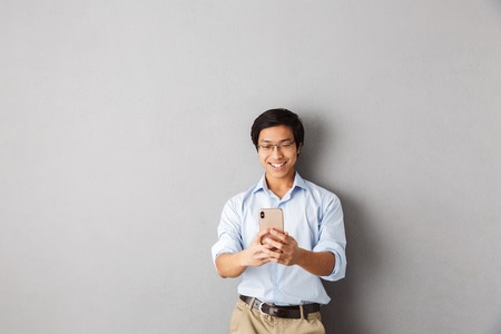 Foto de Smiling asian business man standing isolated over gray background, using mobile phone - Imagen libre de derechos