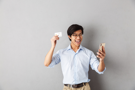 Photo for Smiling asian business man standing isolated over gray background, holding mobile phone, showing plastic credit card - Royalty Free Image