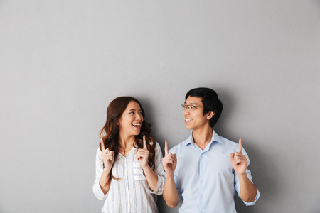 Foto de Cheerful asian business couple standing isolated over gray background, pointing fingers at copy space - Imagen libre de derechos