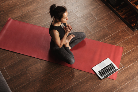 Foto de Beautiful healthy woman doing yoga exercises while sitting on a fitness mat at home, using laptop computer, stretching - Imagen libre de derechos