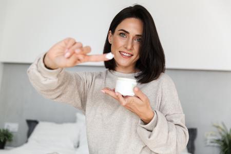 Foto für Image of attractive woman 30s holding jar with face cream in modern bright room - Lizenzfreies Bild