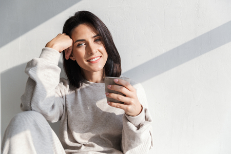Photo for Image of happy woman 30s holding cup with tea while sitting over white wall indoor - Royalty Free Image