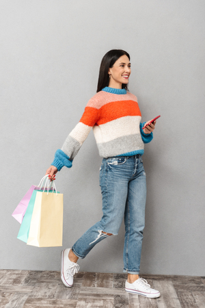 Photo pour Portrait of joyful woman 30s walking with colorful paper shopping bags and cell phone in hands isolated over gray background - image libre de droit