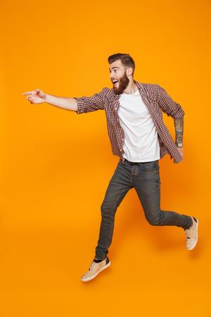 Foto de Full length portrait of a cheerful young man wearing casual clothes running away - Imagen libre de derechos