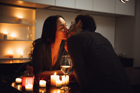 Beautiful passionate couple having a romantic candlelight dinner at home, drinking wine, toasting, kissing