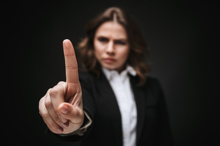 Foto de Portrait of a confident young businesswoman wearing formal suit standing isolated over black background, showing forefinger - Imagen libre de derechos