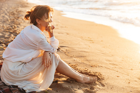 Foto de Image of joyful woman 20s sitting on sand and looking at sea while walking along beach - Imagen libre de derechos
