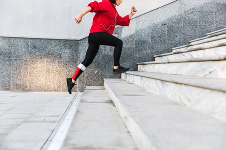 Photo pour Cropped imge of a young sportswoman running up the stairs outdoors - image libre de droit