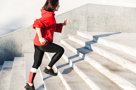 Photo pour Confident young sportswoman running up the stairs outdoors - image libre de droit