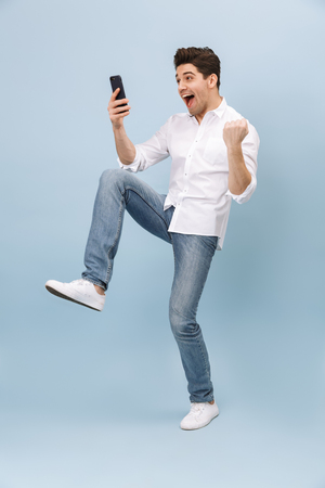 Photo pour Full length portrait of a cheerful handsome young man standing isolated over blue background, holding mobile phone, celebrating - image libre de droit
