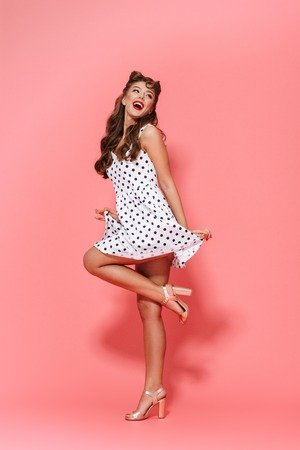 Photo pour Full length portrait of a beautiful young pin-up girl wearing dress standing isolated over pink background, posing - image libre de droit