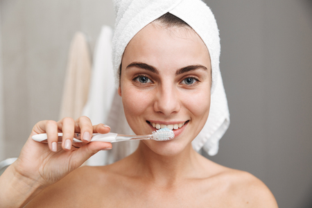 Photo pour Close up of a beautiful young woman with towel on her head standing at the bathroom, brushing teeth - image libre de droit