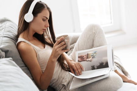 Photo pour Image of beautiful young woman sitting on sofa indoors at home listening music with headphones drinking tea reading magazine. - image libre de droit